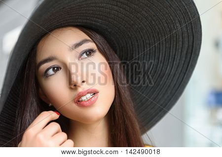 Attractive young girl is looking forward with desire. She is standing in large sunhat