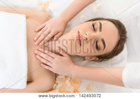 Relaxed girl enjoying massage at beauty salon. Masseuse is pampering her neck with gentleness