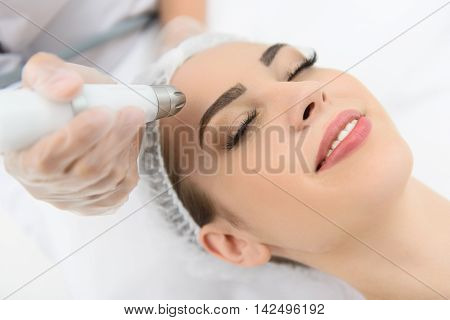 Close up of young girl having stimulating facial treatment at professional clinic. She is smiling with closed eyes