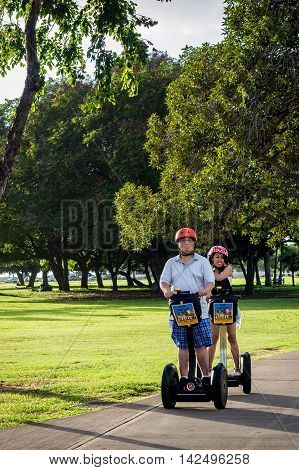 Honolulu, Hawaii, USA - Dec 21, 2015: Ala Moana Park - a couple getting ready for Segway ride as recreation. Segways are commonly on hire in this public park.