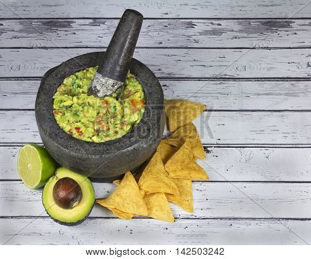 Guacamole with tortilla chips in authentic granite molcajete mortar on old wooden background