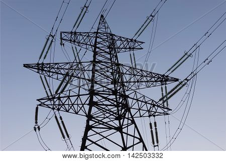 Electric power lines and pylon against blue sky.