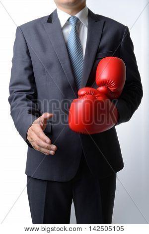 Businessman take off red boxing gloves to offer a handshake on white backgroundcompromise concept