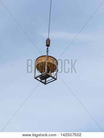 construction. Crane Sling for heavy weight material moving concrete mixer container yellow Cement mixer machine lifting by sling crane with sky in background.