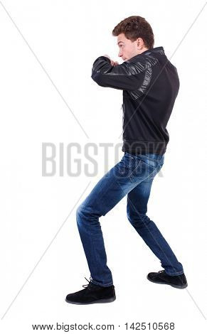 back view of guy funny fights waving his arms and legs. Isolated over white background. Rear view people collection.  backside view of person.  Curly guy in a black leather jacket fights waving his