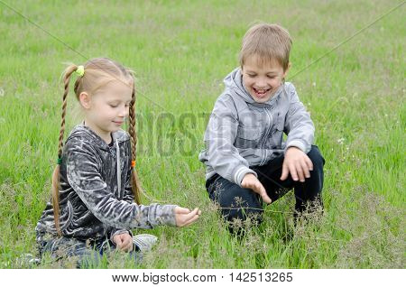cute boy sitting and looking at the girl in the park