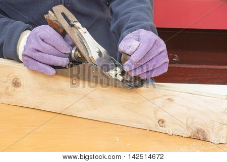 person working, Hands of a carpenter planed wood, on a piece of wood at work in the worksho