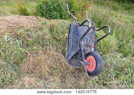An Upturned Wheelbarrow On A Compost Heap