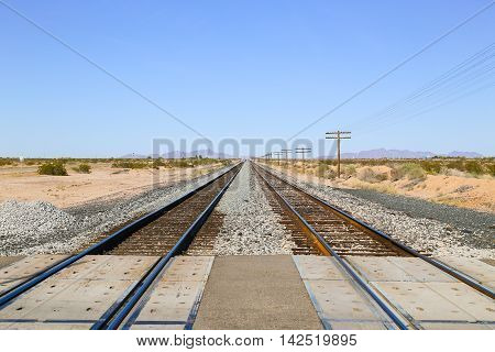 Railroad tracks at a crossing in the Sonoran Desert Arizona USA with overhead power cables to one side and the Old US Highway 80 to the other and a mountain range in the back.