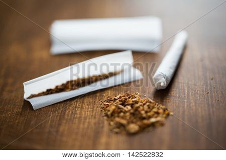 drug use, substance abuse, nicotine addiction and smoking concept - close up of marijuana joint and tobacco