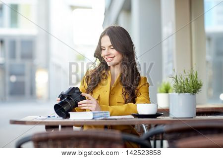 travel, tourism, photography, leisure and people concept - happy young tourist woman or teenage girl with digital camera photographing and drinking cocoa at city street cafe terrace
