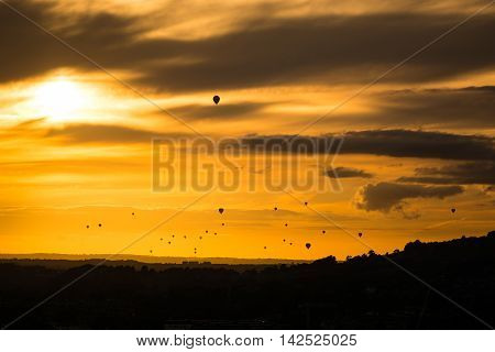 Fleet of hot air balloons in front of sunset. Mass launch at annual Bristol Balloon Fiesta drifts towards the UNESCO World Heritage city of Bath Somerset UK silhouetted in front of setting sun