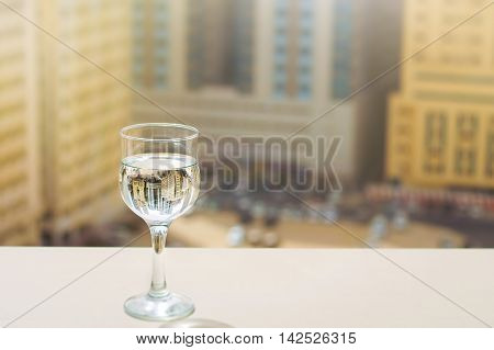 Reflection of Sharjah skyscrapers in a glass of water. View from a balcony on a high level