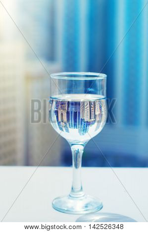 Glass of drinking water with reflection of residential area of Sharjah in UAE