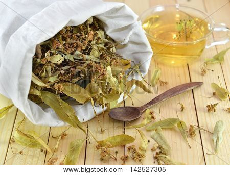 Homeopathic medicine and healthcare still life of dried flowers and leaves of linden in white textile bag and cup of herbal tea over wooden surface background