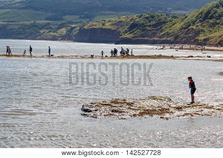 ROBIN HOODS BAY ENGLAND - AUGUST 12: Various people on beach fishing and crabbing. A boy checks his fishing net. In Robin Hoods Bay North Yorkshire England. On 12th August 2016.