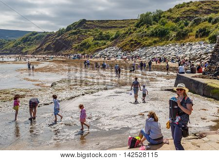 ROBIN HOODS BAY ENGLAND - AUGUST 12: Various adults and children on the beach and in the sea. In Robin Hoods Bay North Yorkshire England. On 12th August 2016.