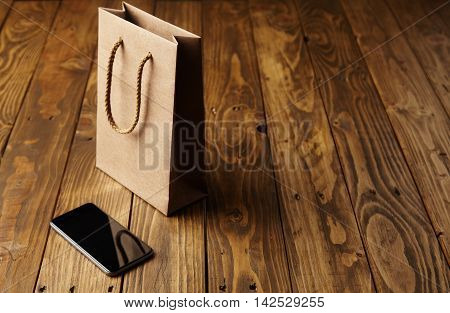 Black Smartphone And Craft Paper Bag On Wooden Table
