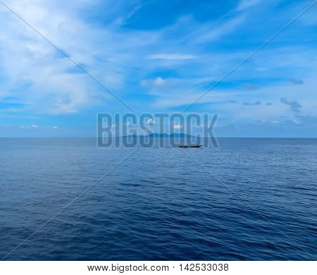 Boat on the sea, on calm water with island in the background