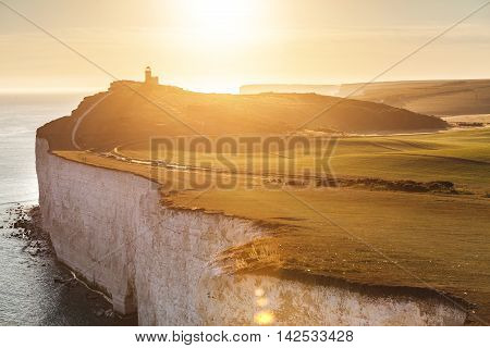 Panoramic view of Seven Sisters cliffs with lighthouse and sea on background at sunset. Photo taken from Beachy Head on Eastbourne side with backlight sunset. Travel and nature concepts.