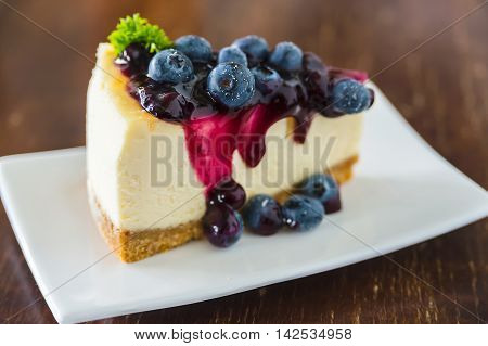 Blueberry cheesecake on white dish on wooden table