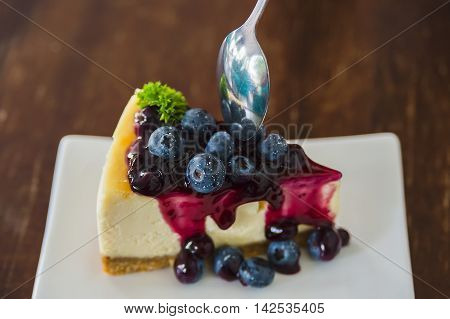 Blueberry cheesecake on white dish with spoon