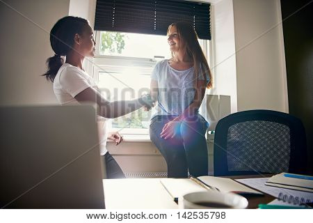 Two successful happy female entrepreneurs in a start-up small business congratulating each other on a milestone shaking hands with elated smiles