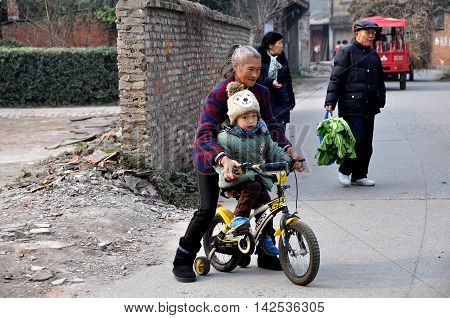 Pengzhou China - December 13 2013: Grandmother teaches her grandson how to ride his bicycle on a rual country road