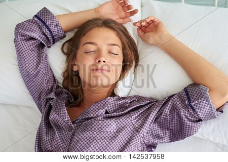 Close-up of charming young woman in pajamas sleeping with her both hands put on pillow above her head