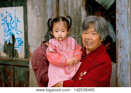 Pengzhou China - September 26, 2006: Grandmother holding her toddler grand daughter in front of their home on Hua Lu (Old Street)
