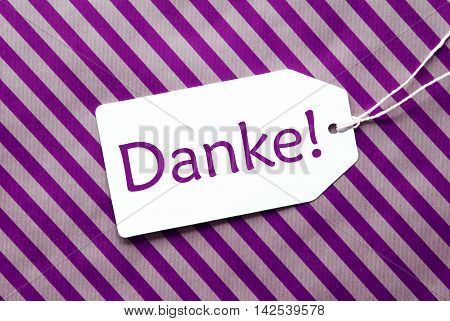 One Label On A Purple Striped Wrapping Paper. Textured Background. Tag With Ribbon. German Text Danke Means Thank You