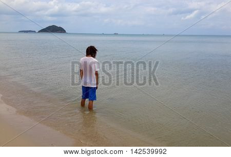 young man with dread locks, white T-shirt, and blue shorts standing in the ocean up his calves, his back to the camera, looking out at the almost flat sea, two islands and boats on the horizon, Songkhla, Thailand