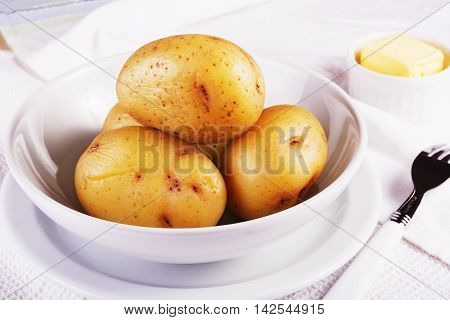Boiled jacket potatoes served in a white bowl with butter