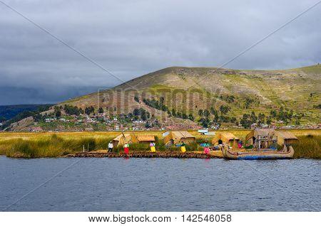 TITICACA PERU MARCH 19 2015: Traditional village on floating Uros islands on lake Titicaca in Peru South America