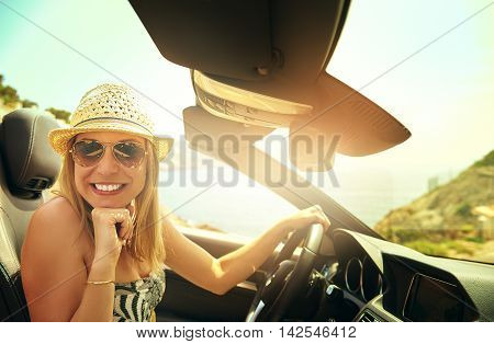 Cute grinning young woman in hat and sunglasses driving convertible car in bright sunlight