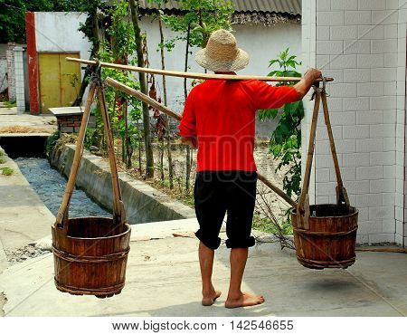 Pengzhou China - May 7 2007: Farmer carrying two wooden buckets suspended from a shoulder yoke in front of his farmhouse