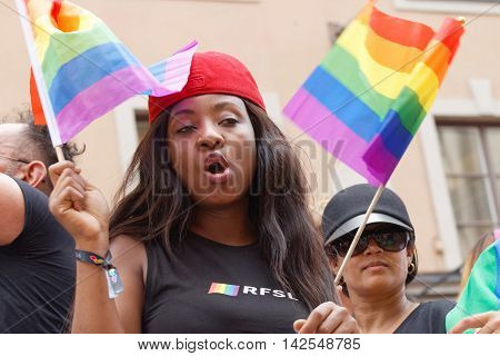 STOCKHOLM SWEDEN - JUL 30 2016: Woman waiving the colorful rainbow Pride flag in the Pride parade in the Pride parade July 30 2016 in Stockholm Sweden