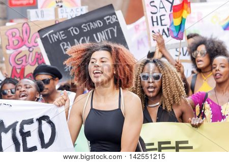 STOCKHOLM SWEDEN - JUL 30 2016: Demonstrating women with afro hair holding a signs in the Pride Parade in the Pride parade July 30 2016 in Stockholm Sweden