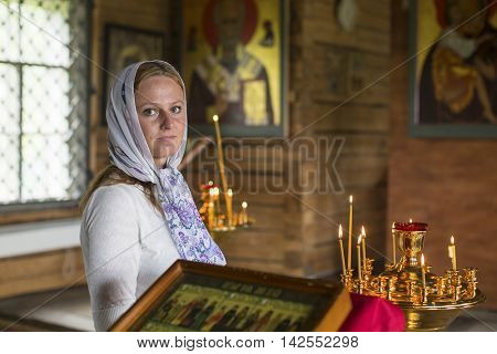 SOGINICY, RUSSIA - JUL 30, 2016: Unidentified parishioner of Church of Nichola. Church of St. Nicholas at Soginicy, the only surviving sample of a steepled Church prionezhskiy school, 1696 built.