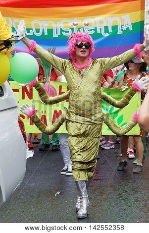 STOCKHOLM SWEDEN - JUL 30 2016: Senior smiling transvestite man with a pink wig dressed as a centipede in the Pride parade July 30 2016 in Stockholm Sweden