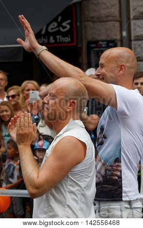 STOCKHOLM SWEDEN - JUL 30 2016: The swedish writer and comedian Jonas Gardell and his man Mark Levengood clapping hands in the Pride parade July 30 2016 in Stockholm Sweden