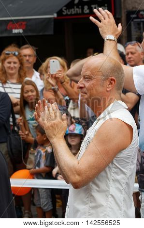 STOCKHOLM SWEDEN - JUL 30 2016: The swedish writer comedian and performer Jonas Gardell clapping hands in the Pride parade July 30 2016 in Stockholm Sweden