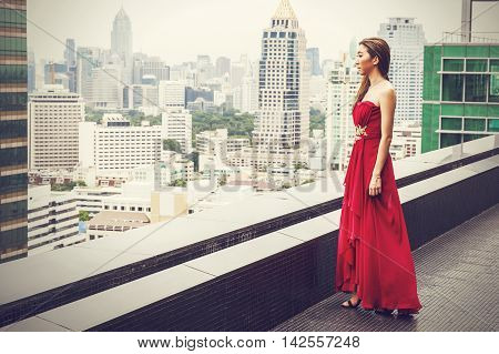 Asian Female Model In Red Evening Dress Standing On The Rooftop Of High Rise Building