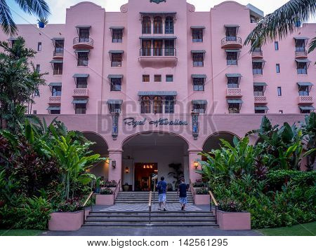 HONOLULU, USA - AUG 8: The refurbished Royal Hawaiian Hotel main entrance with palm and banyan trees providing shade on August 8, 2016 in Honolulu, Hawaii. Photo taken at dusk.