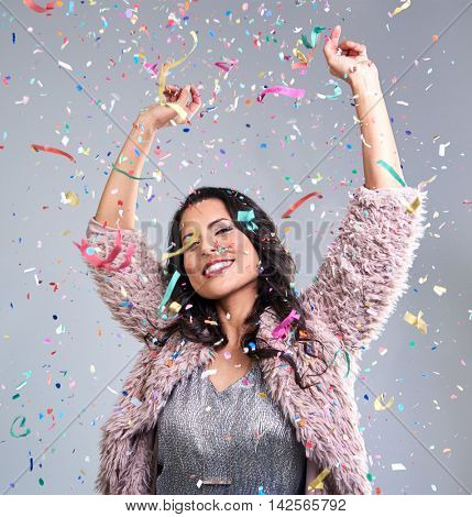 carefree happy woman dancing with arms up at new years eve party falling confetti everywhere