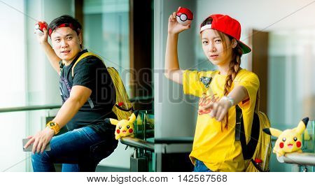 BANGKOK, THAILAND - August 14,2016:  Trainer boy playing pokemon , pokemon ball and Pokemon Go gameplay screenshot on the phone ,Lighting with sun flare