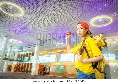 BANGKOK THAILAND – August 142016: Trainer girl playing Apple iPhone5s held in one hand showing its screen with Pokemon Go applicationLighting with sun flare
