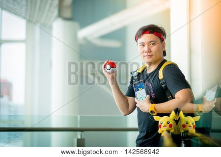 BANGKOK THAILAND – August 142016: Trainer boy playing pokemon pokemon ball and Pokemon Go gameplay screenshot on the phone Lighting with sun flare