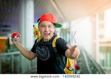 BANGKOK THAILAND – August 142016: Trainer boy playing pokemon pokemon ball Lighting with sun flare