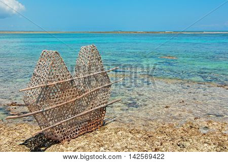Traditional fish trap of palm leaves and wood on the corral rocks of Zanzibar island